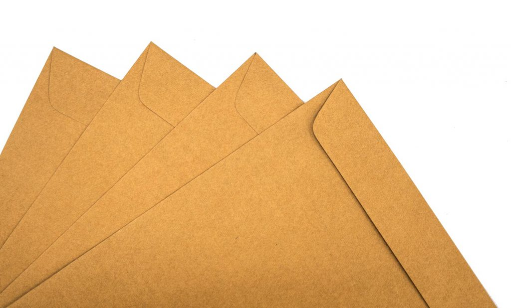 A brown envelope on a wooden floor surface, space for copy.